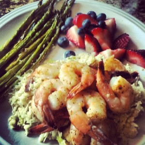Sautéed shrimp on top of cauliflower rice with berries and roasted asparagus.
