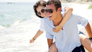 man-woman-piggyback-ride-beach